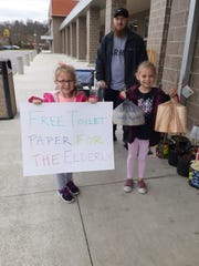 Brian Widener and his daughters Faith, 5 (left) and Cecilia, 6 (right) helped provide free rolls of toilet paper to elderly citizens at Kroger on North Memorial Drive in Lancaster.