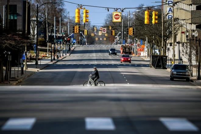 A cyclist crosses an empty Capitol Avenue at the Ottawa Street intersection during rush hour on Wednesday, March 25, 2020, in downtown Lansing. Traffic has been very light while many people work from home during the COVID-19 epidemic.
