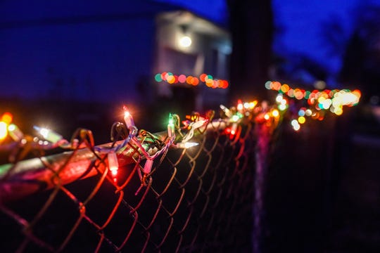 The fence of a home in the Groesbeck neighborhood decorated with Christmas lights photographed on Tuesday, March 24, 2020, in Lansing.