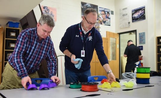 MacDonald Middle School technology teacher Chris DeHaan, left, and Christian Palasty, ELSD director of technology clean N95 masks created with 3D printers, Wednesday, March 25, 2020, at MacDonald Middle School in East Lansing.