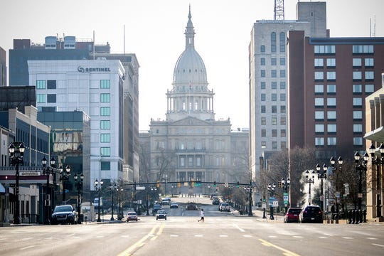 A view of the Michigan State Capitol from an empty Michigan Avenue during rush hour on Wednesday, March 25, 2020, in downtown Lansing.The coronavirus restrictions have reduced traffic significantly.