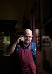 Ernie Mellor, owner of Hog Wild - Real Memphis Barbecue and A Moveable Feast catering company, takes a phone call in the hallway at 1291 Tully St. on Friday, March 20, 2020.