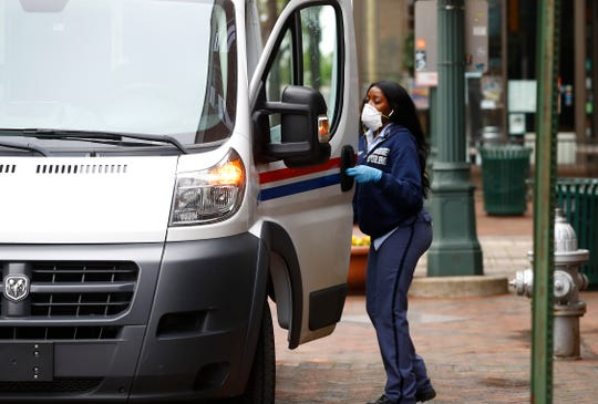 A U.S. postal worker makes her rounds with a protective mask and gloves along Main Street downtown Memphis Wednesday, March 25, 2020.