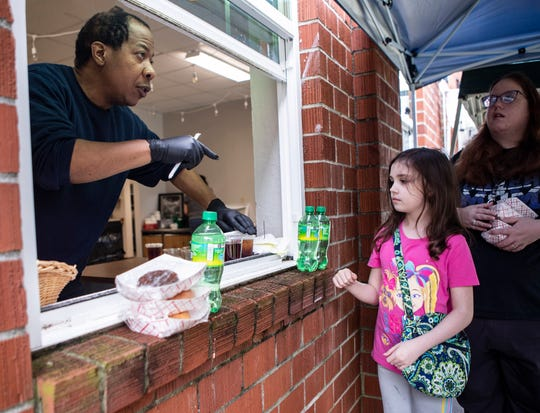 Volunteer Brad Watkins hands out grab-and-go meals through a window at Caritas Community Center and Cafe in Binghampton on Tuesday, March 24, 2020. Caritas Community Center and Cafe offers free daily meals to out-of-work Memphians.