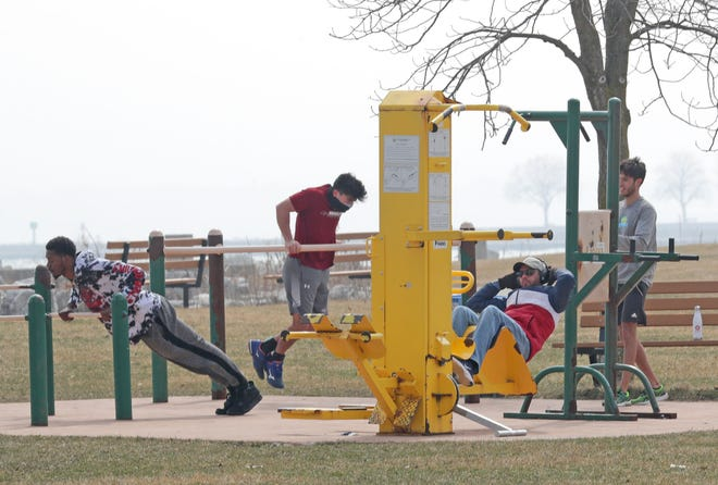 People work out at an exercise station near North Point Park on Lake Michigan Wednesday, March 25, 2020.