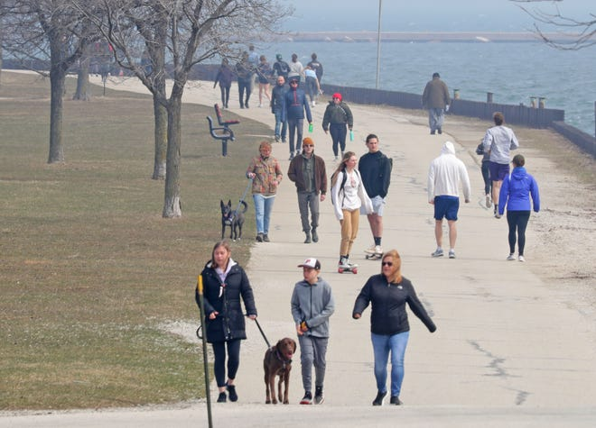 Crowds get fresh air and exercise near Veterans Park on Lake Michigan in Milwaukee on Wednesday, the first full day after Gov. Tony Evers issued a stay at home order to stop the spread of the coronavirus. People were taking advantage temperatures in the 50s.