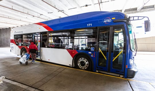 A passenger uses the rear door to board a Waukesha Metro Transit bus on Wednesday, March 25, 2020. Amid the coronavirus pandemic, Waukesha Metro Transit is providing free bus rides, implemented new boarding procedures (using rear door only) for passengers and performing nightly deep cleaning of the buses.
