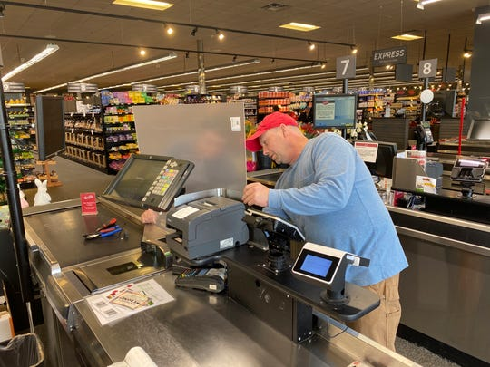 An employee at Sendik's installs a plastic shield at the checkout area of a store on Wednesday, March 25.