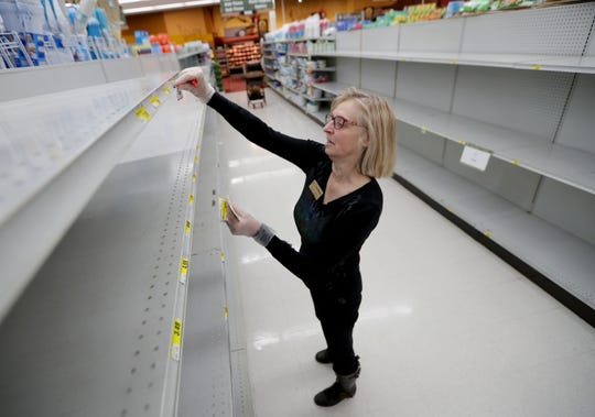 With floral design work mainly gone, Judith Moehr, a floral design manager with Fox Brothers Piggly Wiggly, works on applying price tags to an empty toilet paper aisle at Fox Brothers Piggly Wiggly in Hartland on Wednesday, March 25, 2020.  Supermarket  grocers and employees are now front line workers amid the coronavirus pandemic.