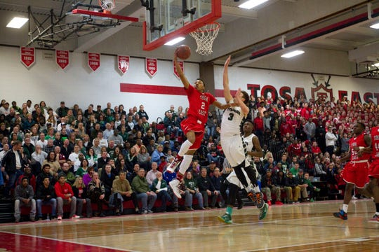 Wauwatosa East's Bryce Beekman (2) goes up for a break-away lay-up past Wauwatosa West's Zach Veit (3) during the the first half the teams WIAA Boys Regional Final game in Wauwatosa East High School Saturday, March 7, 2015, in Wauwatosa, Wisconsin.  East won the game.
