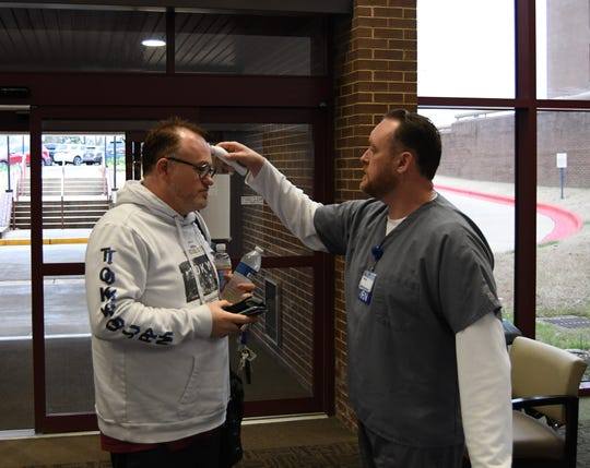 Baxter Regional Medical Center registered nurse Patrick Howald (right) uses a no-touch forehead thermometer to take the temperature of fellow employee Bobby Lowery on Wednesday morning.