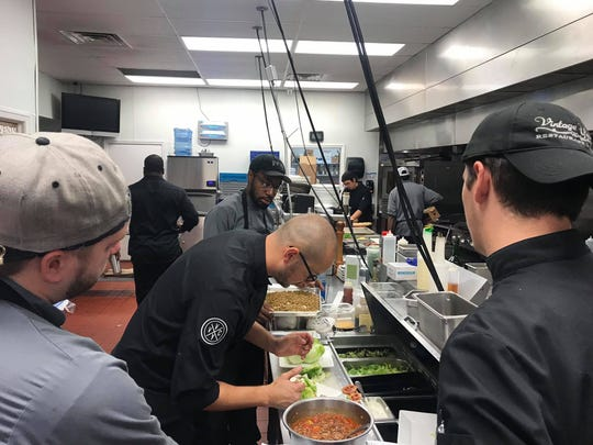 Executive Chef Eric Rivera prepares a dish while Vintage Year kitchen staff observe.