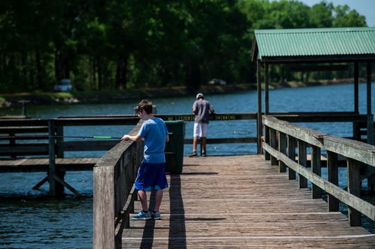 Jordan Brown, 14, and his brother, Jayden, 11, fish at Dallas County Lake  in Sardis, Ala., on Wednesday, March 25, 2020.