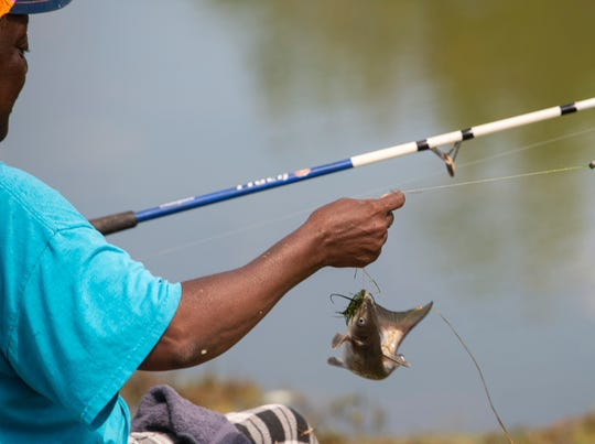 Rosa Doss pulls in a fish at Dallas County Lake  in Sardis, Ala., on Wednesday, March 25, 2020.