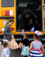 Bus driver Marsha Martin hands out breakfast and lunch to students in their neighborhoods Wednesday, March 25, 2020, in Nashville.