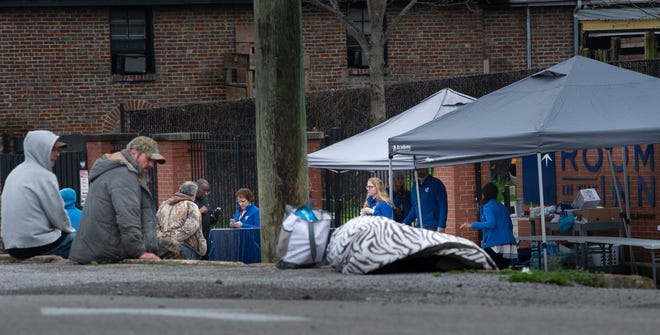 Homeless guests and clients of Room in the Inn wait outside the facility for free lunches Wednesday, March 25, 2020 in Nashville, Tenn. During the Coronavirus outbreak the Room in the Inn is limiting the number of guests or clients into their facilities.