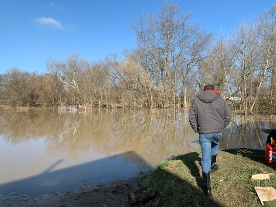 South Newark resident Aaron Holsapple surveys his backyard, which remains flooded after flash flooding hit the Licking County area last week.