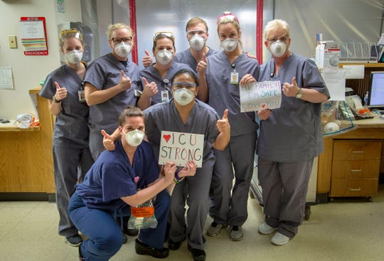 """Holy Name Medical Center in Teaneck, New Jersey, during the first few days of the COVID-19 Pandemic.  03/24/2020  Group photo of ICU nurses. Arlene Van Dyk RN is on the far right holding the sign that says """"Hi Family. I'm safe. I love you."""""""
