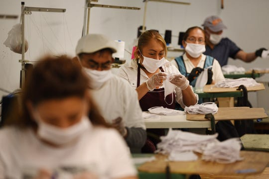 Workers making masks at LBU Inc., in Paterson, NJ on Wednesday March 25, 2020. Until a week ago, LBU Inc., was manufacturing backpacks and cosmetic supply cases. Now it's churning out 100,000 protective masks a week, with plans to double that capacity by next week.