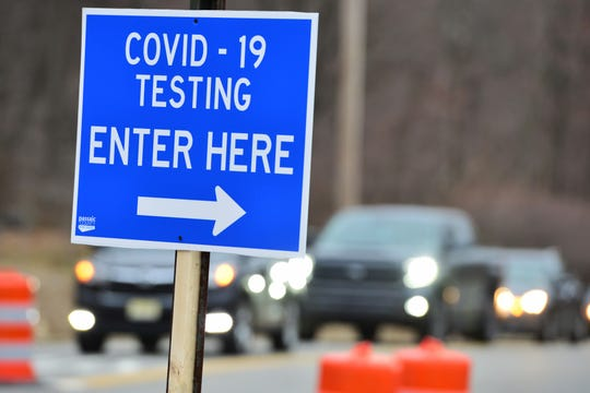 A sign points to COVID-19 testing site in Wayne, New Jersey.