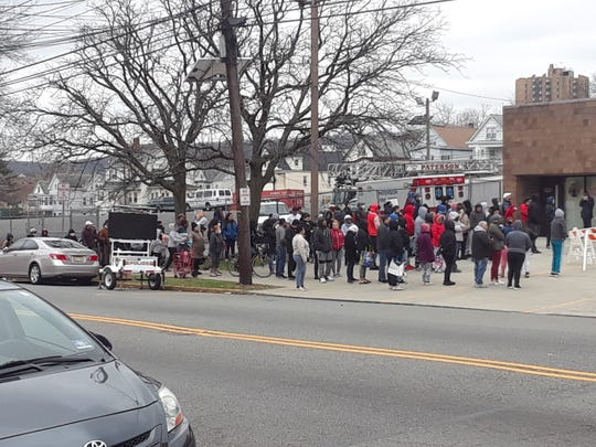 Despite widely-publicized social-distancing guidelines, hundreds of people waited in a tightly-packed line to get free school meals outside Paterson's Madison Avenue firehouse on Wednesday.
