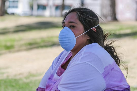 April Hernandez wears a mask while waiting for the bus in Las Cruces on Wednesday, March 25, 2020.