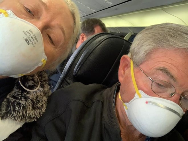 Mary and Jim Laing fly home to Canada with their donated masks safely in place.