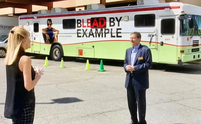 Sandie Newton of NBCares keeps a safe six-foot distance as she speaks with Dr. Frederick Axelrod, CEO of LifeStream.