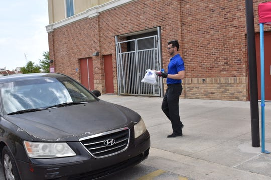 Eric Kroll, the Blue Wahoos food and beverage general manager, delivers a call-ahead order to a customer outside Blue Wahoos Stadium.