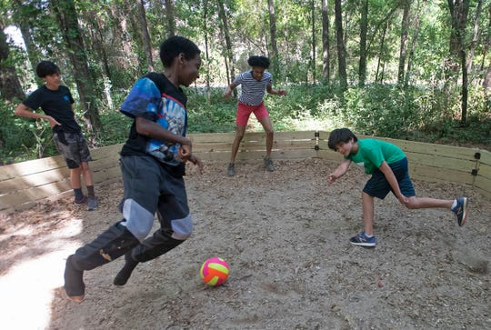 Deon McNair, center, a new YMCA program director,  joins a group of children in a game of Gaga Ball at the Vickery Center on Wednesday, March 25, 2020. The YMCA is working to meet the child care needs of the area's first responders during the COVID-19 scare.