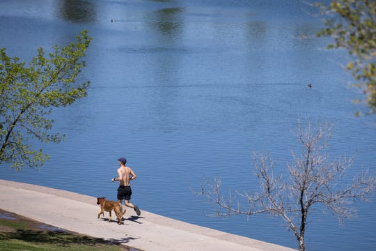 A man runs with his dog on March 24, 2020, at Kiwanis Park in Tempe, Ariz.