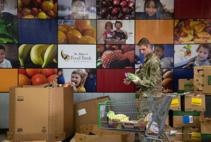 Arizona Army National Guard Spc. Owen Mayotte assembles a food box on March 25, 2020, at the St. Mary's Food Bank Alliance in Phoenix.