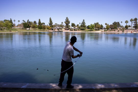 Danny Saenz fishes on March 24, 2020, at Kiwanis Park in Tempe, Ariz.