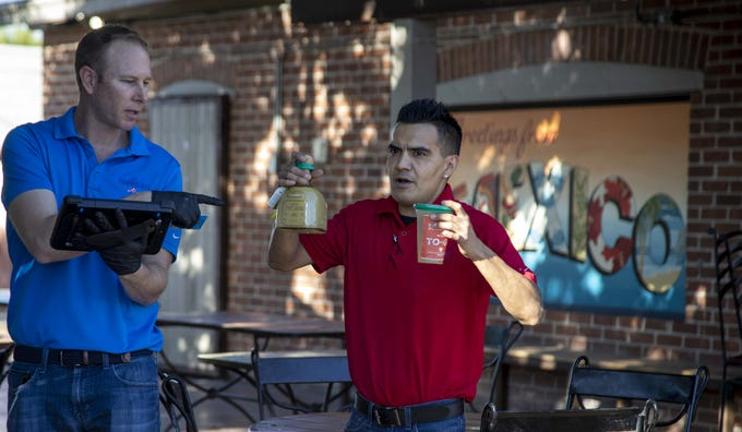 Kurt Riske, an owner of Los Sombreros, with manager Mikey Garcia, talk to customers about their choice of drink on March 24, 2020.