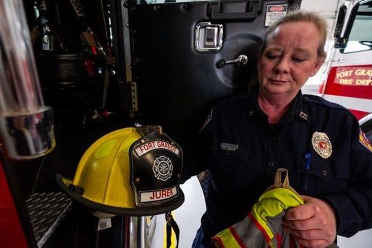 Fort Gratiot Firefighter/EMT Deb Nichols-Jurek takes her helmet and coat out of a firetruck Tuesday, March 3, 2020, at Fort Gratiot Fire Department.