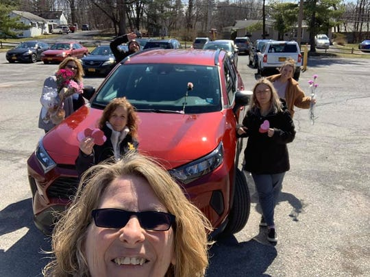 Alyssa Plastini, Heather Cooper, Ryan Oakley, Christine Weir, Victoria Weir, Karen Reilly and Dani Plastini pose for a photo as they place notes and flowers on essential workers' cars.