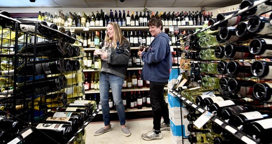 Julie Widmayer, left, and Leigh Reigle, both of the Etters area, shop during a liquor run at Maryland Line Wine & Spirits Wednesday, March 25, 2020. The store is experiencing an influx of Pennsylvania shoppers after the state's liquor stores have been closed due to the Covid-19 pandemic. The women and 2 other friends carpooled for the 45-minute trip to the liquor store, which is located just south of the state line in Parkton, Md. Bill Kalina photo