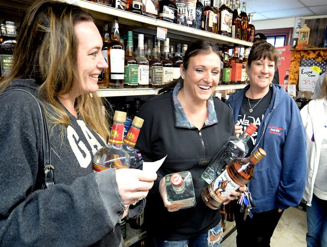 From left, Julie Widmayer, Amanda Houtz and Leigh Reigle, all from the Etters area, make a liquor run at Maryland Line Wine & Spirits Wednesday, March 25, 2020. The store is experiencing an influx of Pennsylvania shoppers after the state's liquor stores have been closed due to the Covid-19 pandemic. The group of friends carpooled for the 45-minute trip to the liquor store, which is located just south of the state line in Parkton, Md. Bill Kalina photo