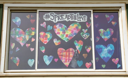 Tiffany Loucks' picture window is decorated with hearts. Loucks started the Spread The Love Facebook page that encourages people to construct a heart, and put it in your window, to share the love with others.