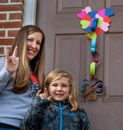 Tiffany Loucks, right, stands with her 7-year-old son Carter in front of one of her door hearts showing the hands sign for love.