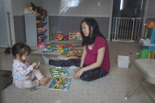 Alaina Wong-Canissario has her two-year-old daughter Sierra Canissario, work on a puzzle in their Penfield home on March 25, 2020.  She is expecting her second baby in two weeks.