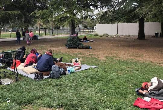 A group of  homeless people sit outside the Redding Library on Monday. Some homeless say it is more difficult to find basic necessities during the coronavirus pandemic.