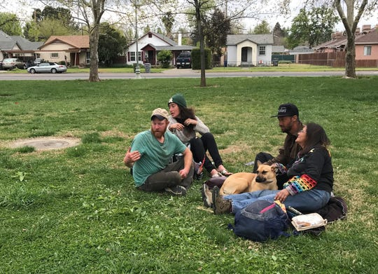 Derick Erwin, left, Tamara Avery, Tristan Thomas and Amanda Marsh sit together out on the lawn by Redding City Hall.