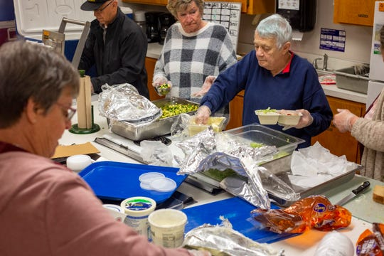 Mary Sue Andrews, in her fourth-year volunteering for Meals on Wheels, scoops salad into a meal at the First Presbyterian Church in Woodburn, on March 25, 2020. In order to follow social distancing guidelines, the organization is switching to frozen meals and spreading out the work stations.