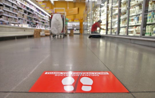 A sign on the floor at the H-E-B store on the west side of San Angelo reinforces the practice of social distancing as employees prepare for customers Wednesday, March 25, 2020.