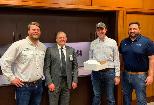 A donation of restaurant gift guards is made to Ochsner LSU Health Shreveport CEO Chuck Daigle (second from left). From left, Billy Hargrove of Hargrove Roofing, Grant Nuckolls of Twisted Root and Cassidy King of Pizza Rev.