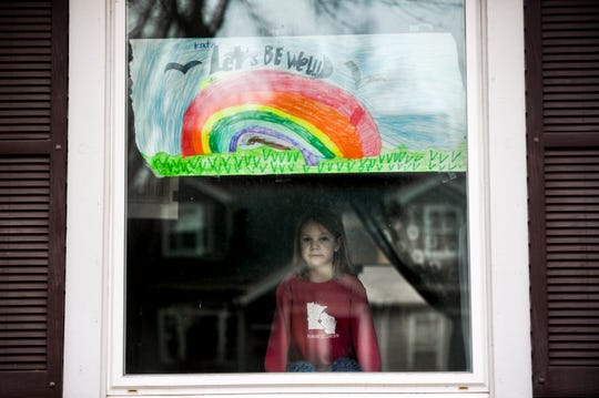 Kate Madsen, 6, displays her drawing in her window in hopes that it would cheer her neighbors up on Wednesday, March 25, 2020 in Sioux Falls.