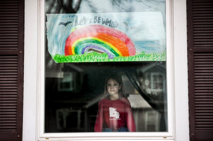 Kate Madsen, 6, displayed her drawing in her window in hopes that it would cheer her neighbors up on Wednesday, March 25, 2020 in Sioux Falls, S.D. Madsen and her first-grade classmates were learning remotely to prevent the spread of the coronavirus at Robert Frost Elementary School.