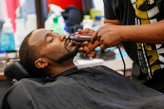 George Mathis gets in a hair cut and beard trim at Reflection Barber Shop on Wednesday, March 25, 2020, the day before Springfield's stay-at-home order takes effect. Barber Shops and Hair Salons are considered nonessential businesses and will be closed during the mandatory order.