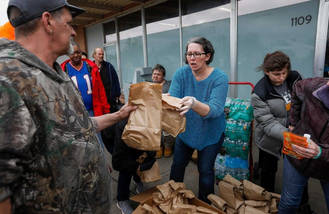 Christie Love, in blue, hands out food. She is in the frontlines in caring for the homeless during the pandemic.